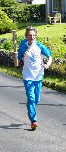 Jim Lutomski carrying the Queen's Baton